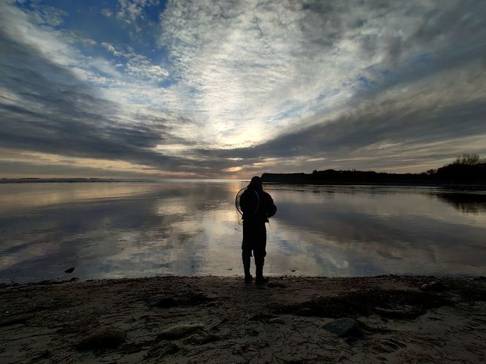 Rear view of man standing on beach against sky during sunset