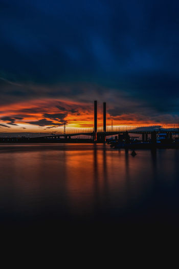 Expect the unexpected. From a Moody, cloudy weather to an epic sunset.... Melbourne truly is amazing 💜 My Best Photo Waterfront Calm Water Water Reflections Golden Hour Sunset Beauty In Nature Bridge Factory Water Urban Skyline Gas Sunset Oil Industry Scenics Idyllic Tranquil Scene Horizon Over Water Atmospheric Mood Tranquility