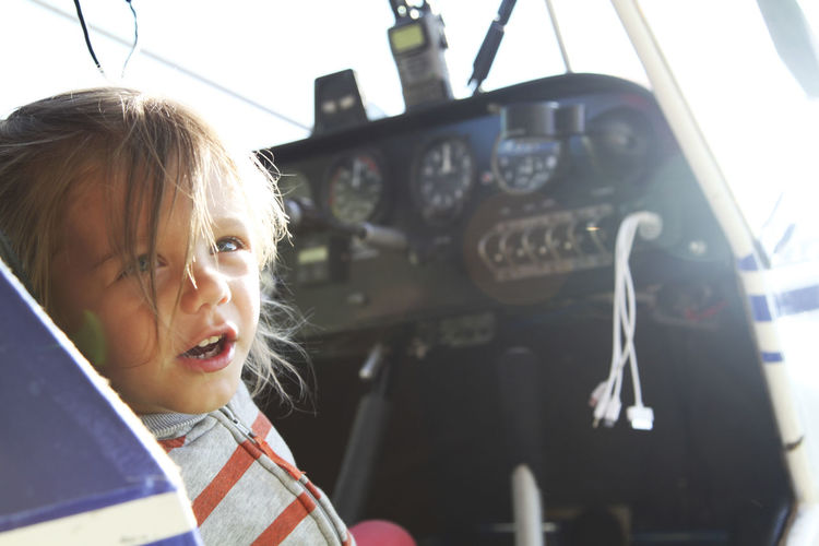 Close-up of cute girl sitting in air vehicle