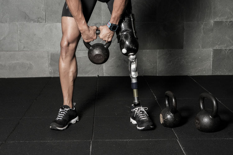 Low section of disabled man exercising with kettlebell at gym