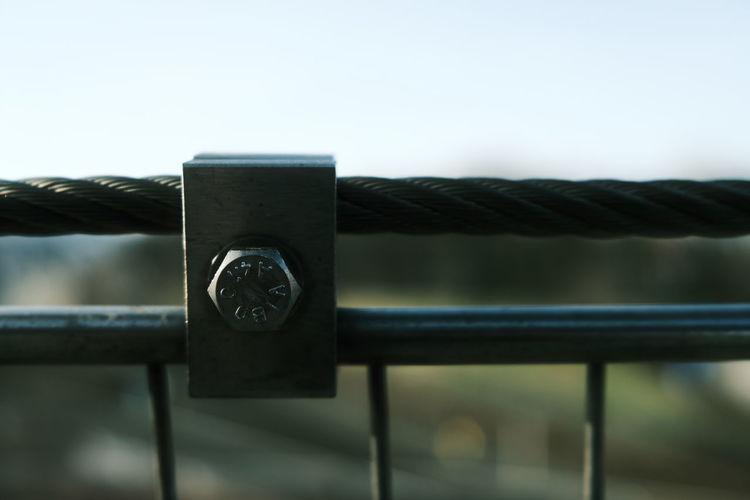 Close-up of padlock on railing against sky