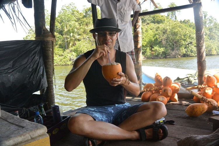 Portrait of man drinking coconut water while sitting on boat in river
