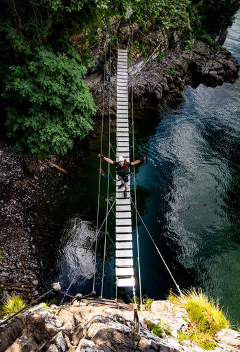 Adventure Beauty In Nature Bridge Bridge - Man Made Structure Bridge On Water Day Footbridge Full Length Group Of People High Angle View Men Nature Outdoors People Real People RISK River Rock - Object Rope Water Young Adult