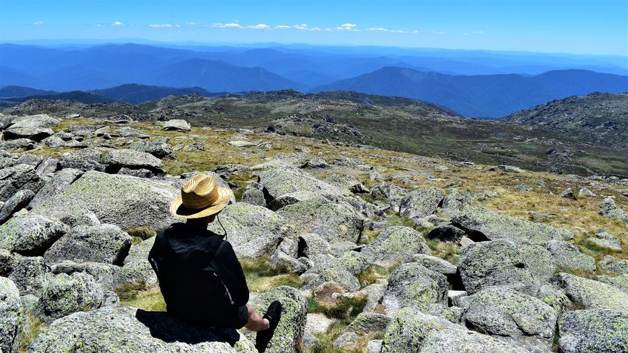Rear view of man sitting on top of mount  kosciuszko looking at mountains