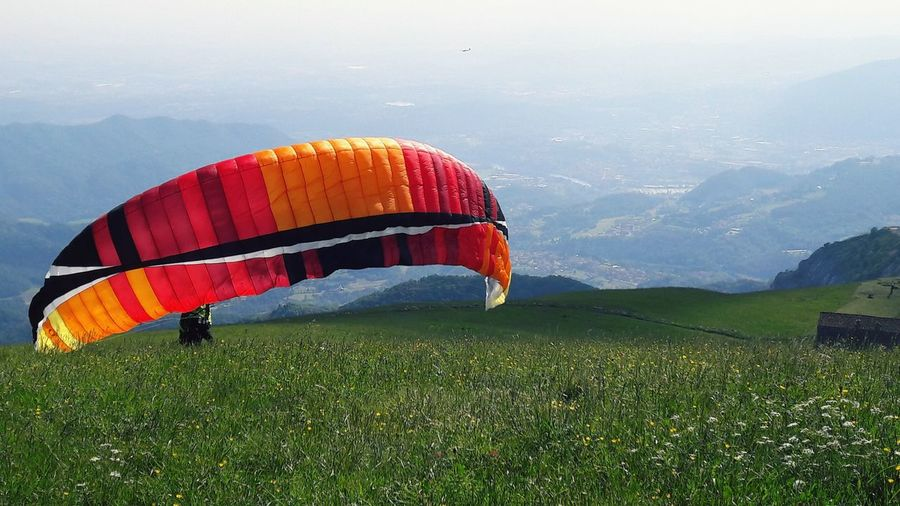 parachute Kite Kite Flying Fly Flying Hot Air Balloon Mountain Adventure Dawn Sky Grass Landscape Parachute Paragliding Extreme Sports Agricultural Field Flight Foggy