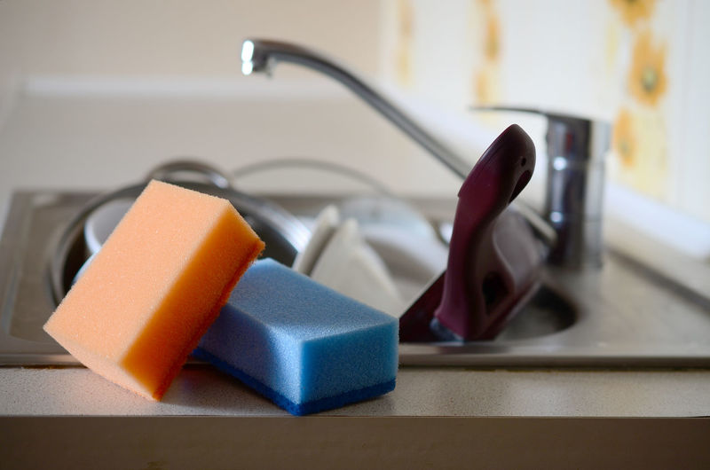 Cleaning sponges on kitchen sink full of dishes