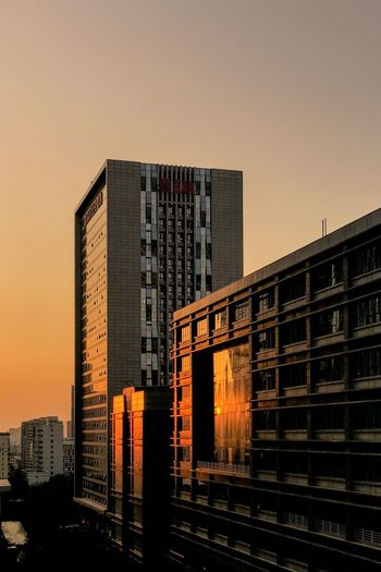 Modern buildings against sky during sunset