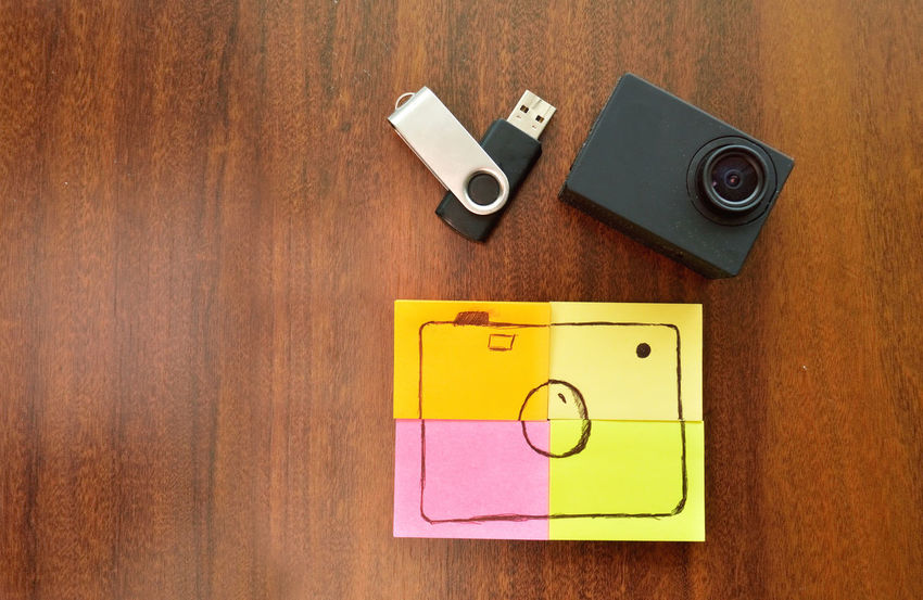 Sticky notes with a camera drawing along with a pen drive and an action camera over a wood table Camera Memories Close-up Day Indoors  No People Pen Drive Post It Wood - Material