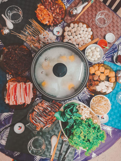 High angle view of steamboat and food on table