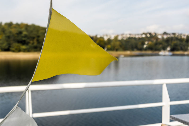 Close-up of yellow flag against sky