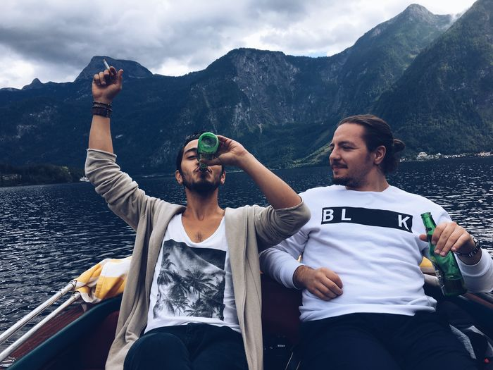 Friends sitting on boat in mountains