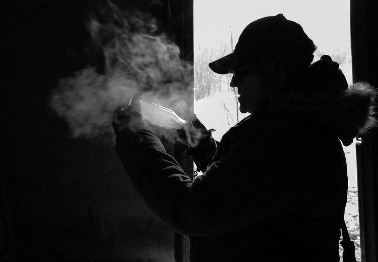 Man Inserting Cigarette Smoke In Glass Bottle