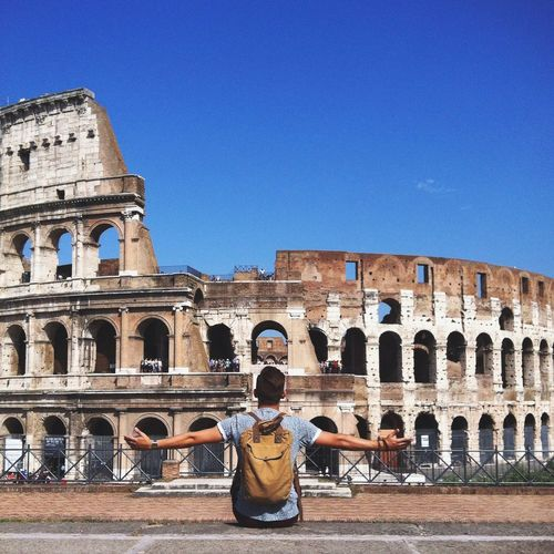 Rear view of man sitting with arms outstretched by colosseum against clear blue sky