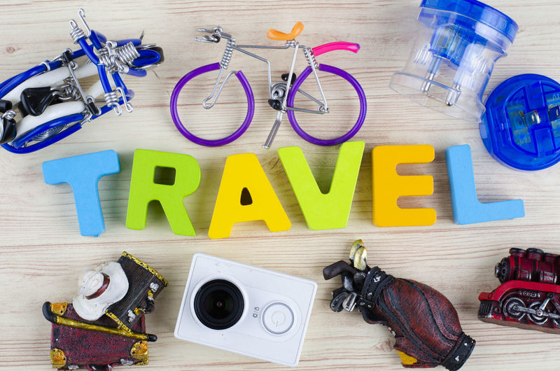 top view vacation and holiday concept word TRAVEL with accessories on wooden background High Angle View Directly Above Indoors  Table Still Life Large Group Of Objects Camera - Photographic Equipment Photography Themes No People Wood - Material Text Equipment Group Of Objects Multi Colored Photographic Equipment Scissors Glasses Choice Variation