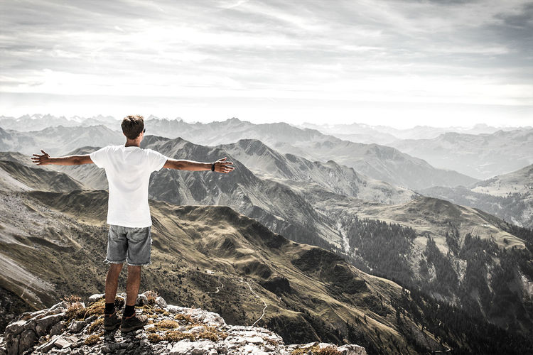 Rear View Of Man With Arms Outstretched On Top Of A Mountain In The Alps