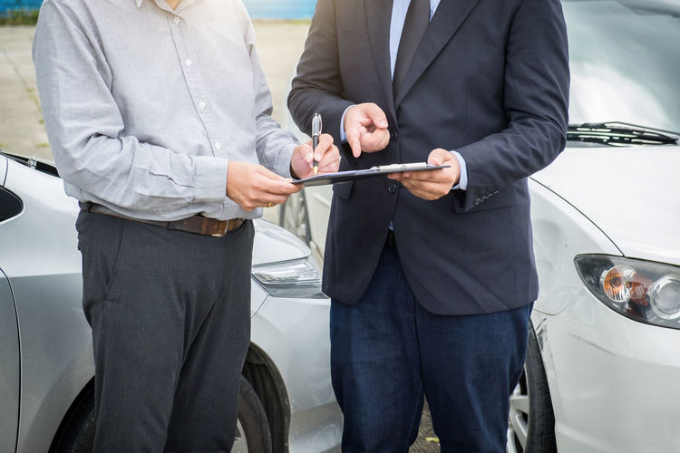 Midsection of businessman signing document with male coworker against cars