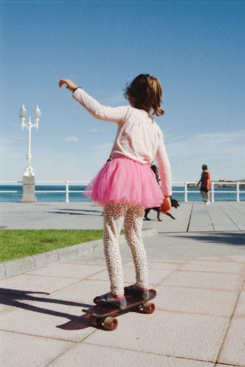 Girl Skateboarding On Promenade Against Sky
