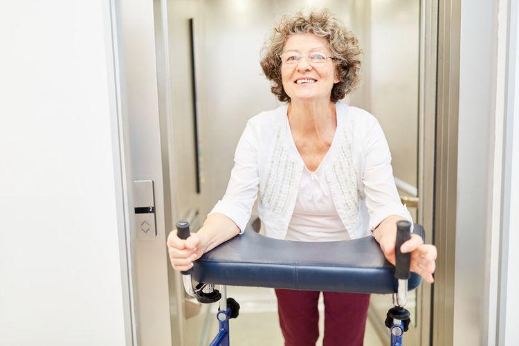 Portrait of smiling woman walking with walker in nursing home