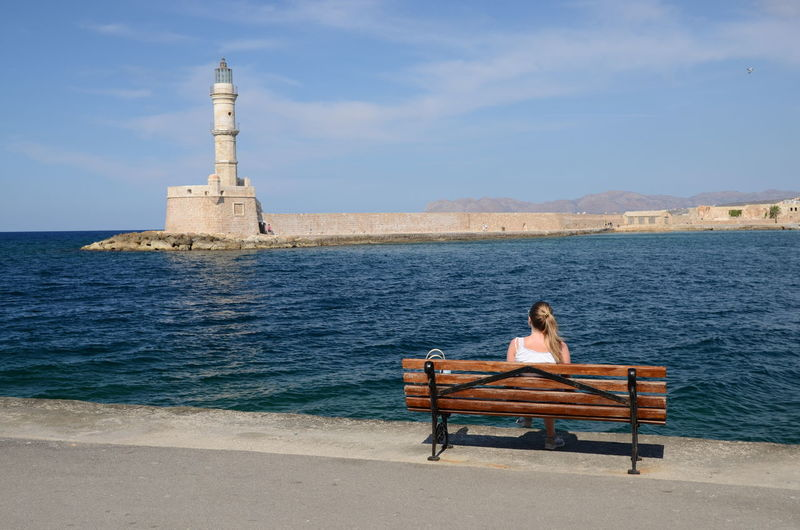 Rear view of woman sitting on bench against lighthouse in sea