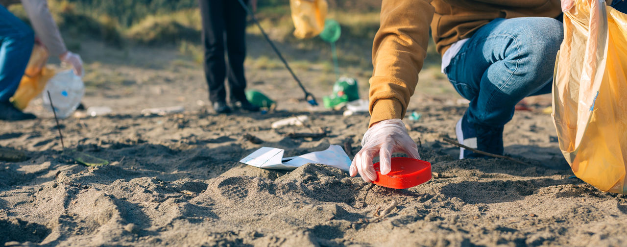 Low section of people cleaning at beach