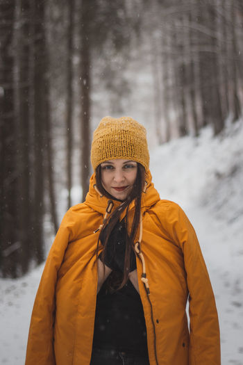 Portrait of smiling woman standing in snow during winter