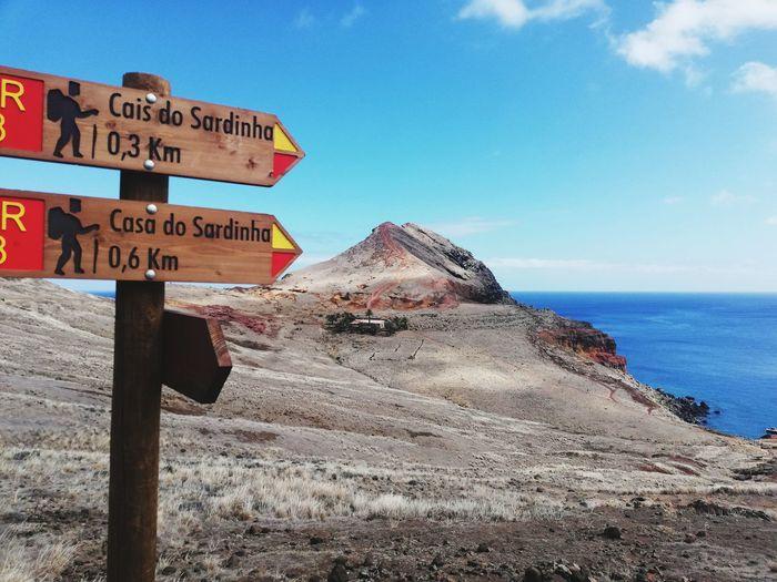 Information sign on land against sky