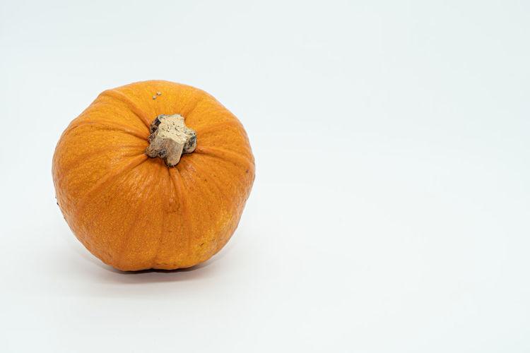 Close-up of pumpkin against orange background
