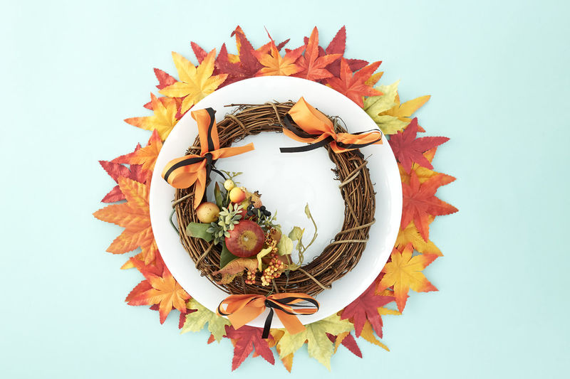 White dish with wreaths and autumn leaves decorative Halloween on pastel pale blue background, with copy space for text. Flat lay. Sales Holiday Flyer Banner Poster Travel Traveling Traveler Vacation Trip Sale Template Mockup Abstract Art Autumn Leaves Falling 2019 2020 Wreath New Year Halloween Autumn Leaves Autumn Background Plate Minimal Flat Lay Fall Background Leaf Design Frame Orange Concept Composition Green Maple Bright Pattern Forest Decoration Art And Craft Creativity Indoors  No People White Background Studio Shot Representation Still Life Close-up Craft Celebration Animal Representation Shape Plant Part