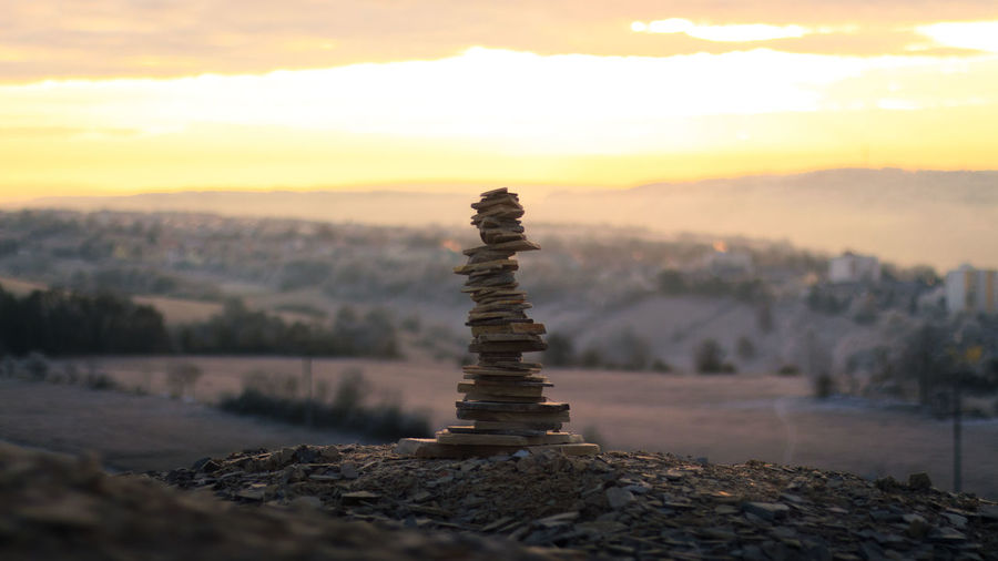 Close-up of stack of rocks against sky during sunset