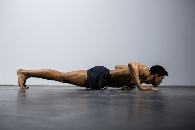 A fitness model performing push ups. Profile. Adult Asian  Athlete Body & Fitness Exercise Human Body Man Nam Vo Profile Shirtless Sportsman Deltoid  Detemination Fitness Model Grey Wall Handsome Hunk Male Muscle Muscular Build One Person Push Ups Strength Training Studio Shot Torso