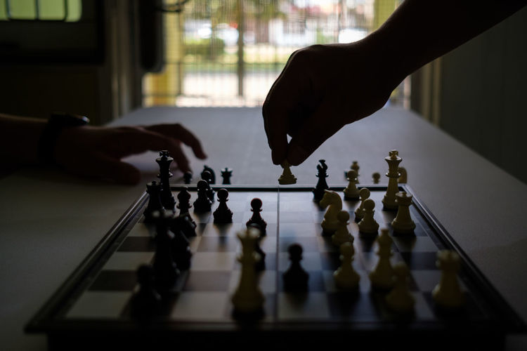 Low angle view of people playing on chess board