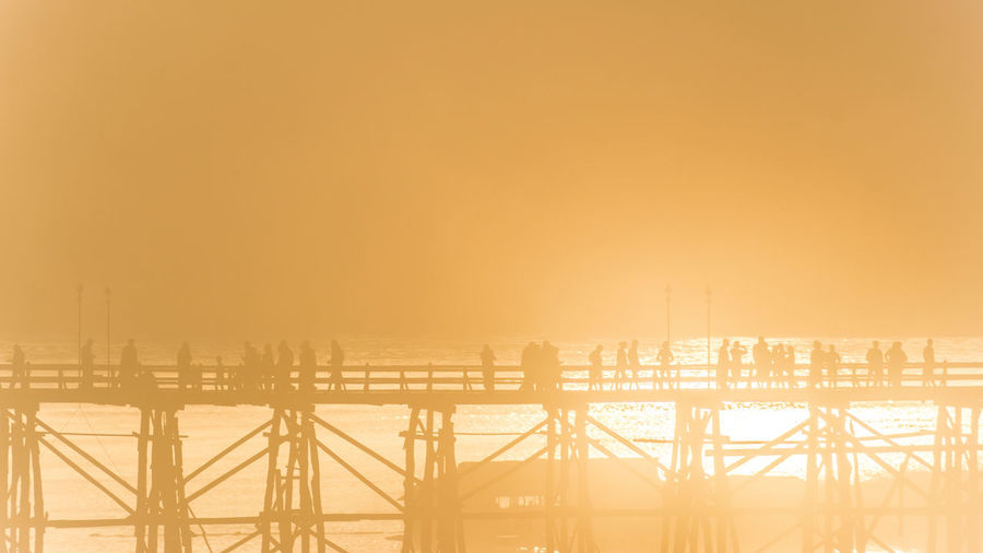 Silhouette people walking on mon bridge at sangkhla buri district against sky
