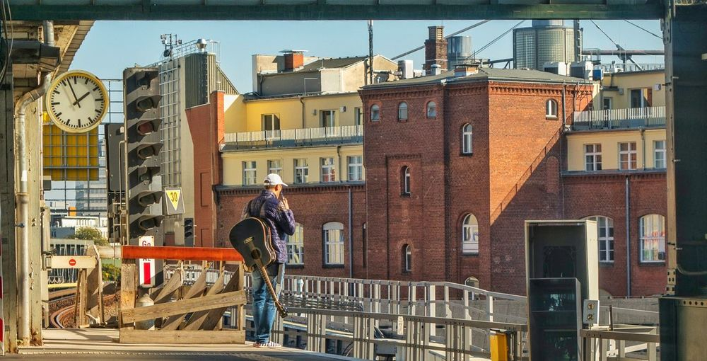 Rear view of man with guitar standing at railroad station