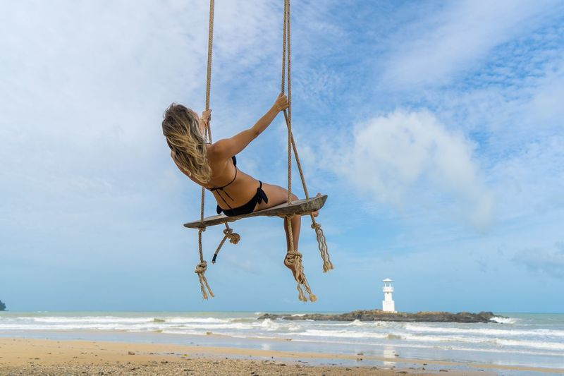 Low angle view of woman swinging at beach against sky