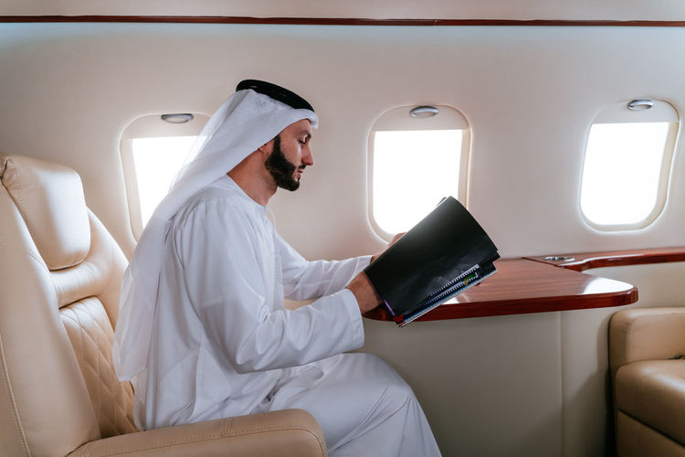 Smiling businessman traveling in corporate jet