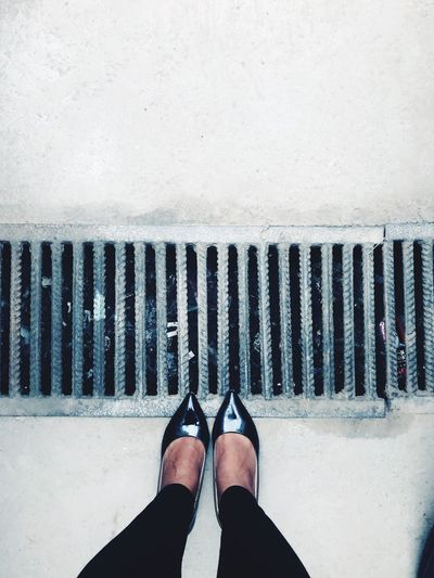 Low section of woman standing by drain on footpath