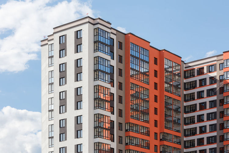 New high apartament building with multiple balcony and windows on blue sky with white clouds