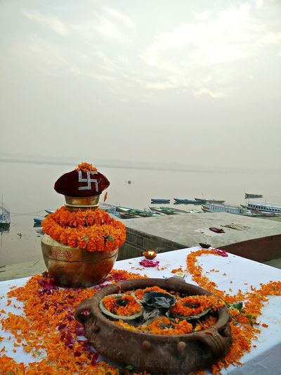 Lota and religious offerings at assi ghat against ganges river