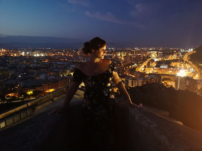 Woman standing by illuminated buildings in city at night