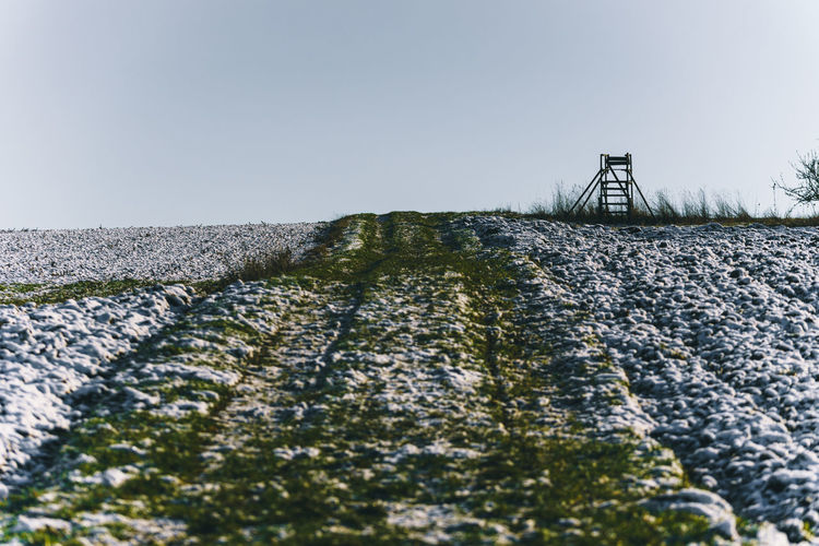 Surface level of snowy field against clear sky