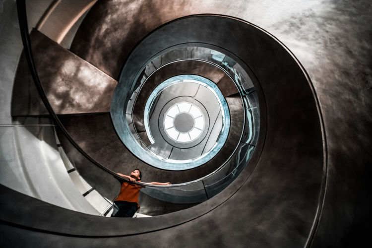 Low angle view of boy standing on spiral staircase