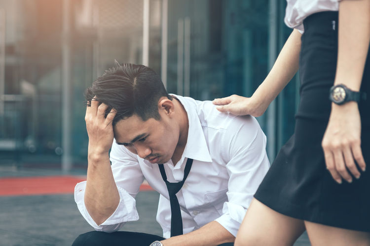 Midsection of businesswoman consoling stressed businessman sitting against office building