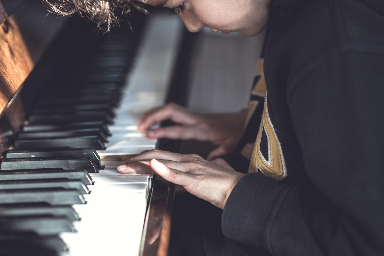 Midsection of boy playing piano
