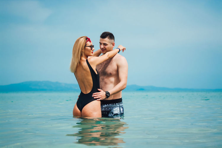 Couple Happiness Love Adult Bonding Couple - Relationship Emotion Heterosexual Couple Leisure Activity Lifestyles Love Men Outdoors Positive Emotion Real People Sea Shirtless Togetherness Two People Water Young Adult Young Men Young Women