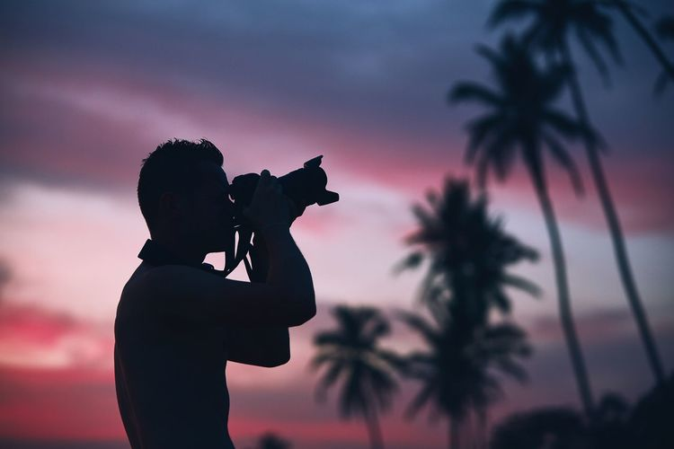 Silhouette of the young photographer with camera against palm tree at colorful sunset. Man Photography Photographer Photographing Sunset Sunrise Sky Moody Sky Skill  Creativity Photography Themes Silhouette One Person Camera - Photographic Equipment People Palm Tree Holding Nature Cloud - Sky Technology Tropical Climate Inspiration Real People Nature Silhouette