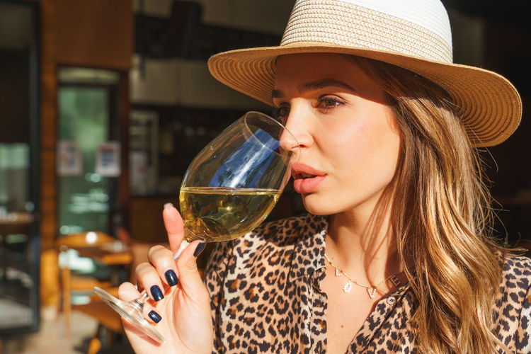 Young woman drinking wine at restaurant