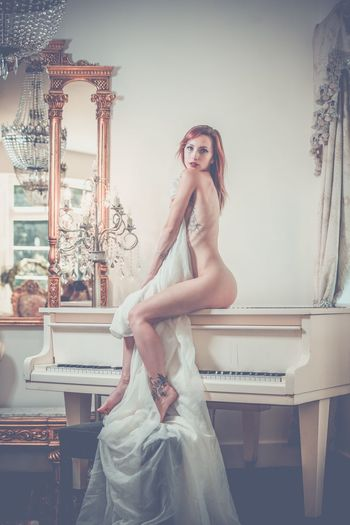 Side View Portrait Of Naked Woman Sitting On Piano At Home