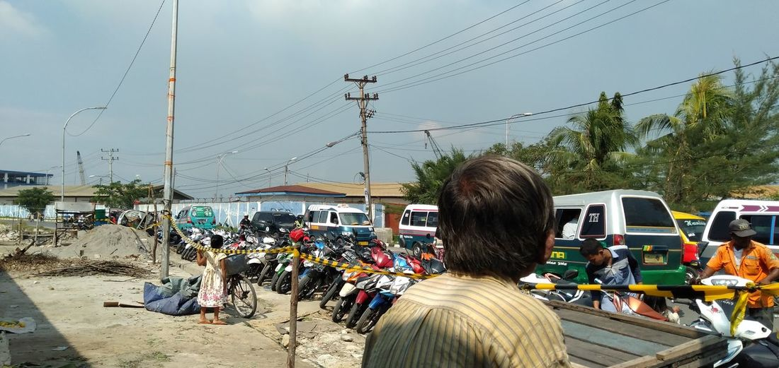 Rear view of people on road against sky
