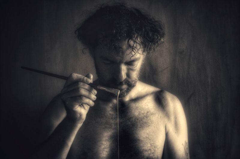 Shirtless man holding paintbrush against wall