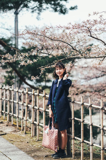 Sakura One Person Tree Real People Plant Leisure Activity Lifestyles Young Adult Standing Front View Portrait Looking At Camera Smiling Casual Clothing Nature Young Women Three Quarter Length Women Full Length Fashion Beautiful Woman Outdoors Hairstyle Cherry Blossom Sakura Sakura Blossom